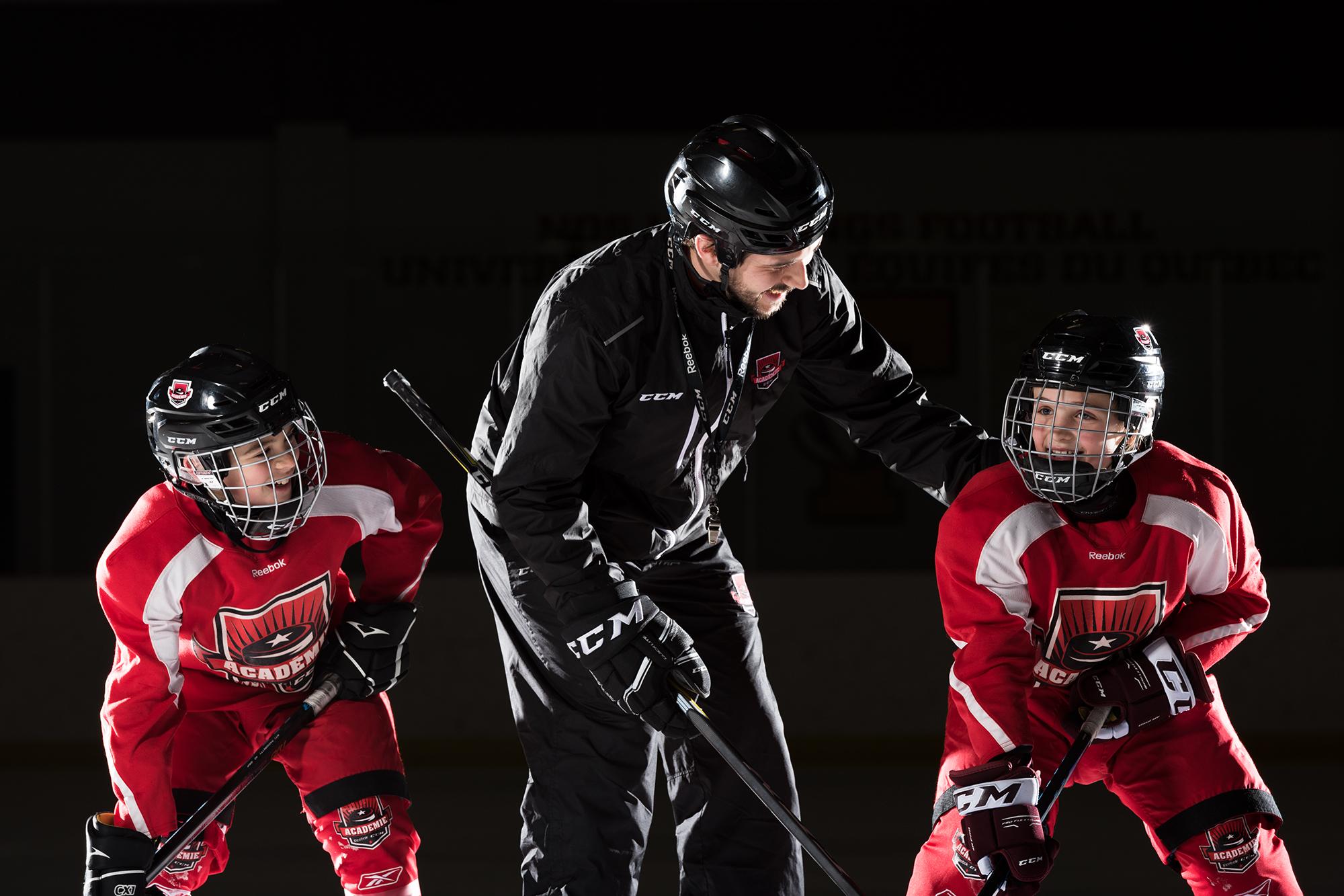 entraîneur qui explique des notions à de petits joueurs de hockey sur la glace