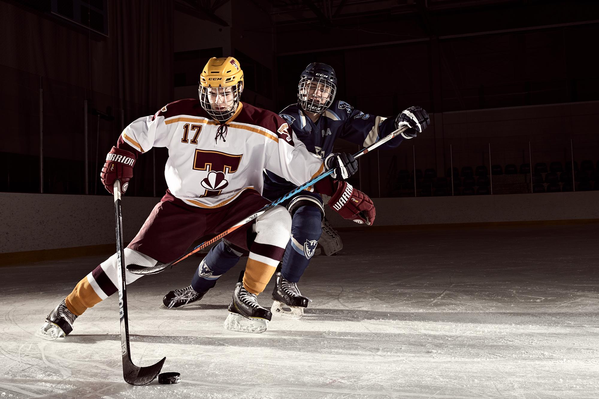 joueur de hockey protégeant la rondelle devant un adversaire