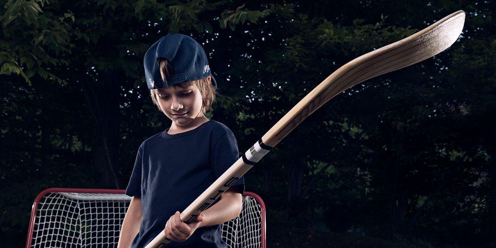 jeune garçon avec bâton de hockey Sher-Wood dans les mains